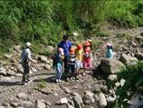 學童於溪邊觀察水域生態